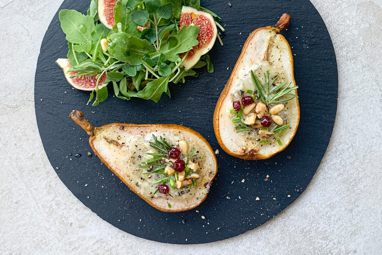 2 gefüllte Birnenhälften auf einem schwarzen Schieferteller mit Beilagensalat und Feigen