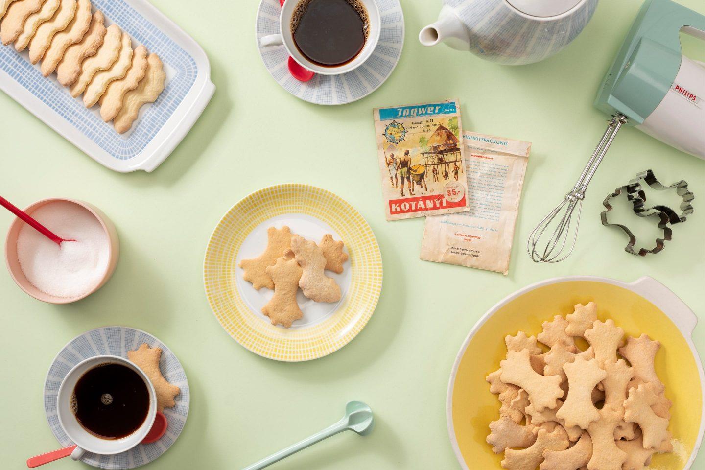 Джинджифилови бисквити върху чиния за торта и комплект чаши за кафе в пастелни цветове.