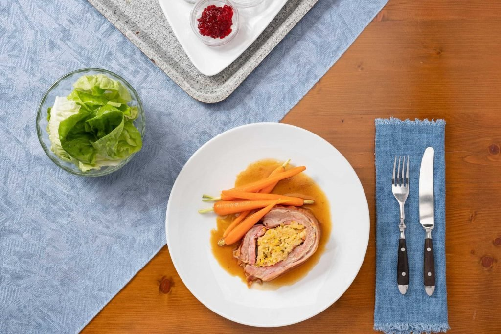 Две парчета пълнени телешки гърди с глазирани моркови, поднесени в бяла чиния.