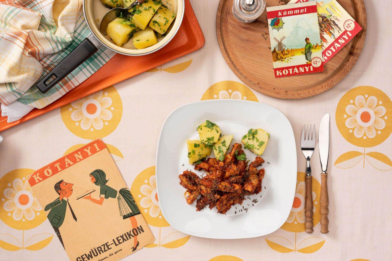 Порция подправено с кимион свинско месо, поднесено върху леко квадратна чиния с картофи с магданоз.