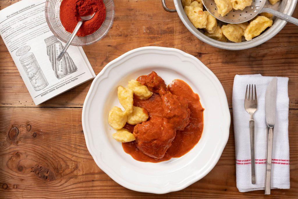 Дълбока чиния с пиле с червен пипер и кнедли, до която има купа пълна със смлян червен пипер.