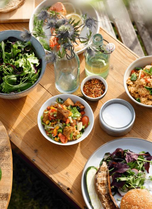 Различни салати, подредени на масата.